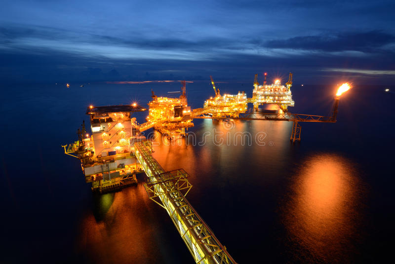 The large offshore oil rig drilling platform at night. With twilight background stock photography