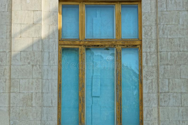 Large old blue window with a brown frame on the gray stone wall stock image