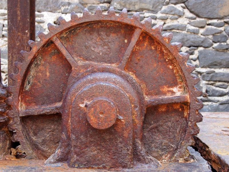 Large old rusty cogwheel on obsolete heavy machinery against a stone wall stock photos