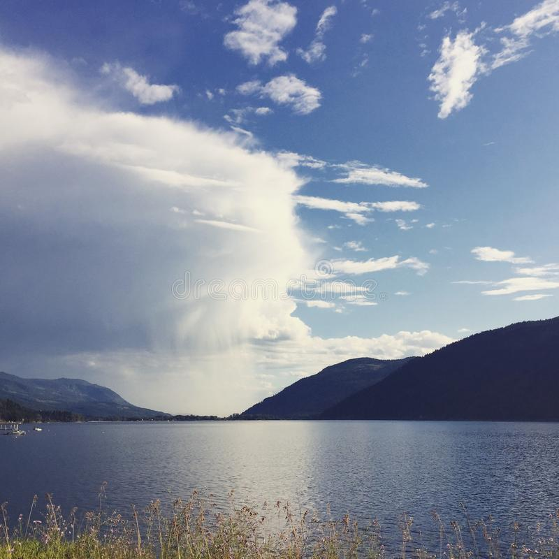 Large ominous thunder cloud at lake royalty free stock image