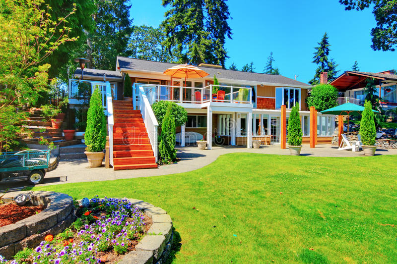 Large orange house with white trim. View of back yard with patio area. stock photo