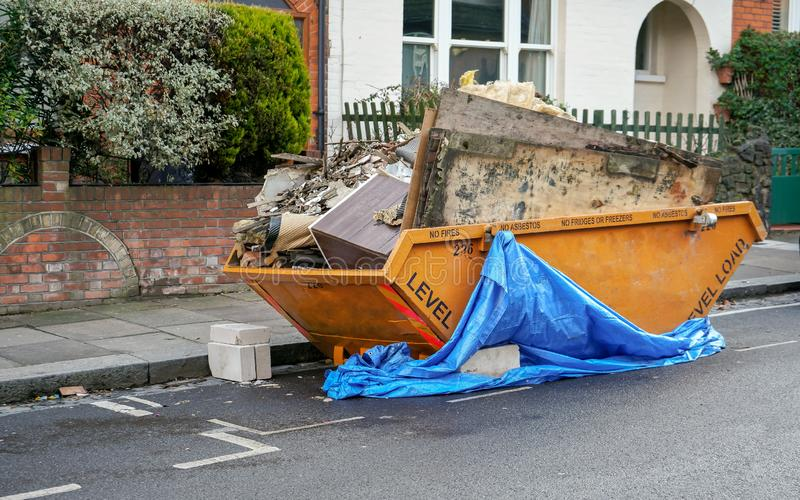 Large orange metal skip container in front house, full of rubbish from household reconstruction.  stock photography