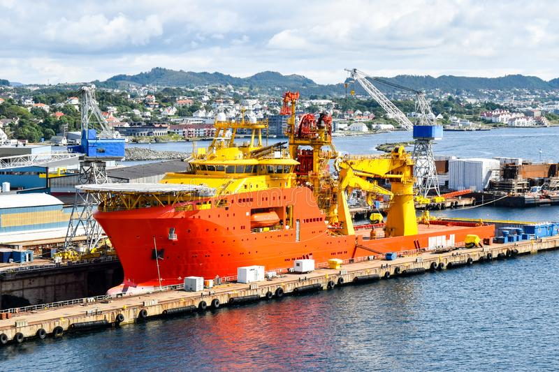 A large orange and yellow colored Offshore Construction Vessel OCV is in a dry dock of a shipyard and is being repaired stock photo