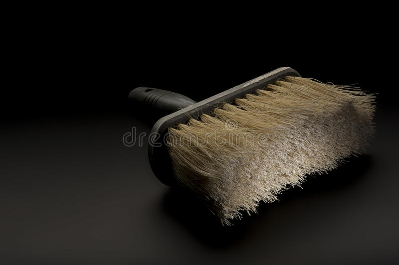 Large paintbrush or wallpapering brush. Close up view of a new clean large paintbrush or wallpapering brush lying on a dark background conceptual of DIY, home stock photography