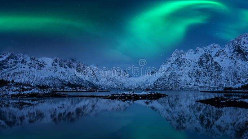 Northern lights, Aurora borealis, Lofoten islands, Norway. Night winter landscape with polar lights, starry sky and mountains stock photos