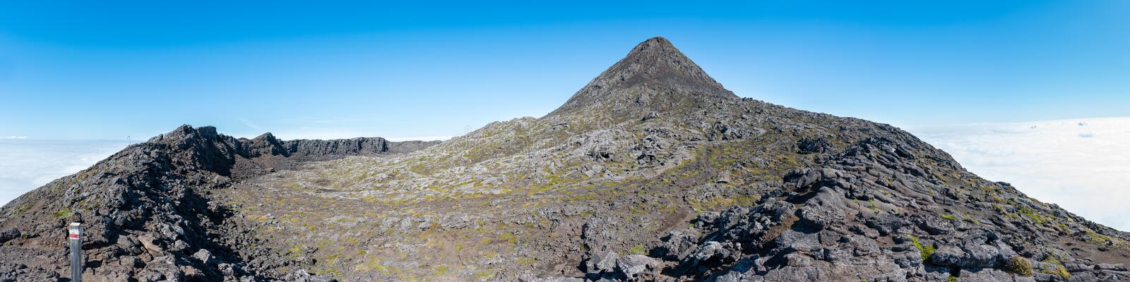Large panoramic view of the pit crater rim and the pinnacle of the stratovolcano Mt Pico on Pico Island of the Azores. At 2351m, the summit is the highest royalty free stock image