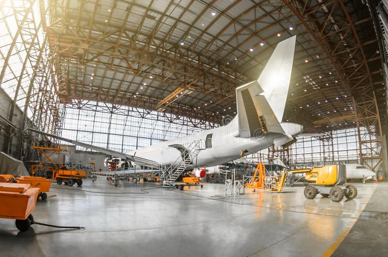 Large passenger aircraft on service in an aviation hangar rear view of the tail, on the auxiliary power unit. Mechanization of the. Tail is dismantled stock photo