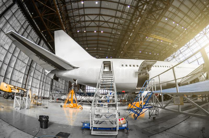 Large passenger aircraft on service in an aviation hangar rear view of the tail, gangway ladder entrance. royalty free stock image