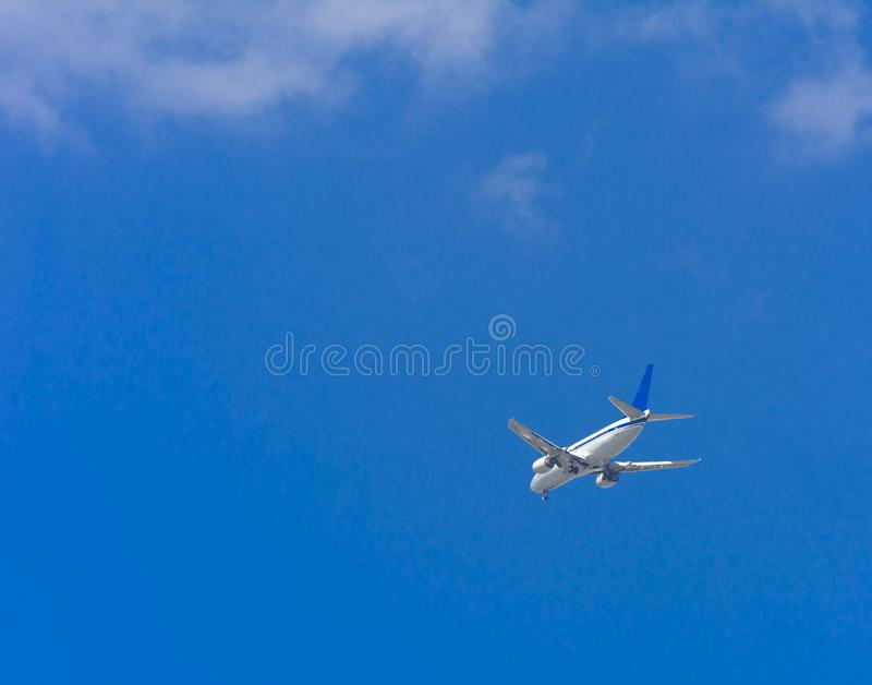 A large passenger airliner is a plane with a big wingspan high i. N the sky. Transport tourists for exotic holidays against the blue sky and white clouds royalty free stock images