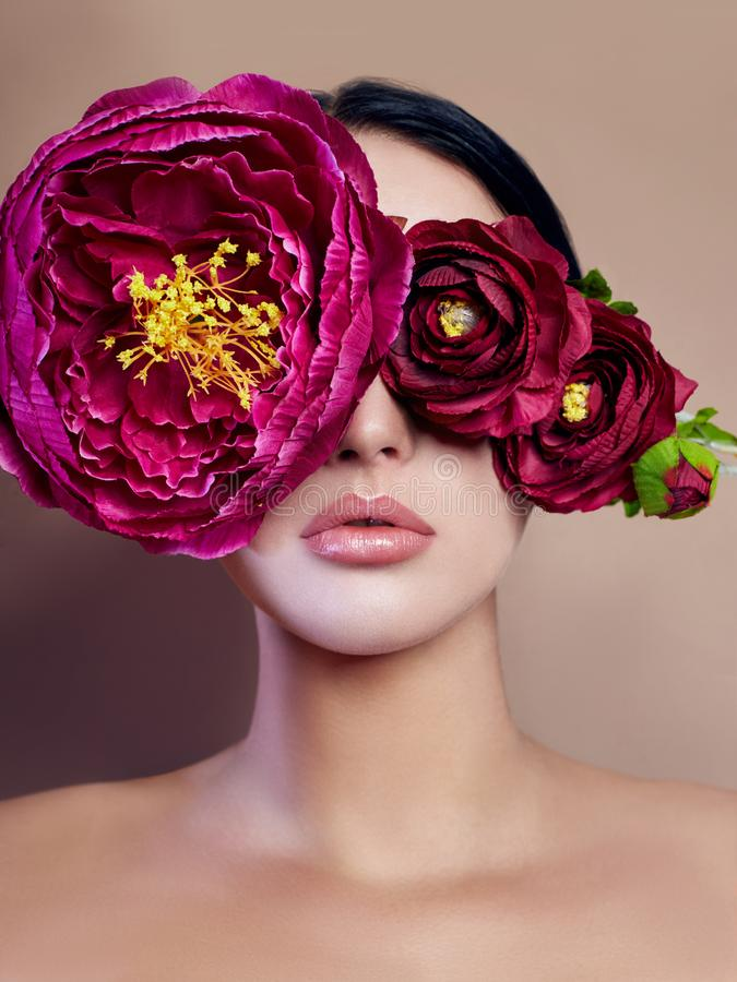 Large peonies near a woman face, art fashion flowers in front of a girl, nature face care, natural cosmetics. And professional makeup, beige background. Purity stock image