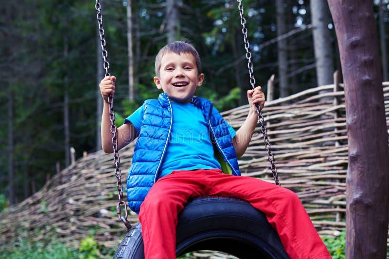 Large petit garçon de sourire s'asseyant sur l'oscillation de pneu photos libres de droits