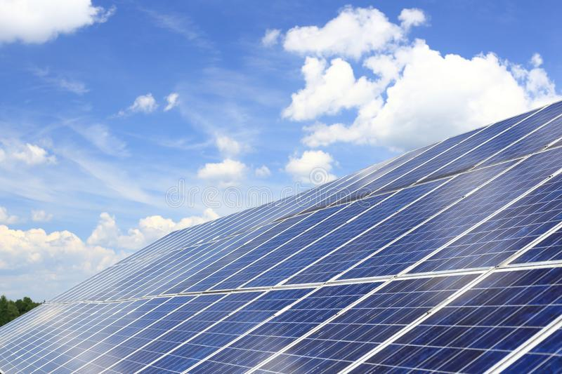 Large photovoltaic arrangement with sky background. Large photovoltaic arrangement on a roof top of a building stock photography