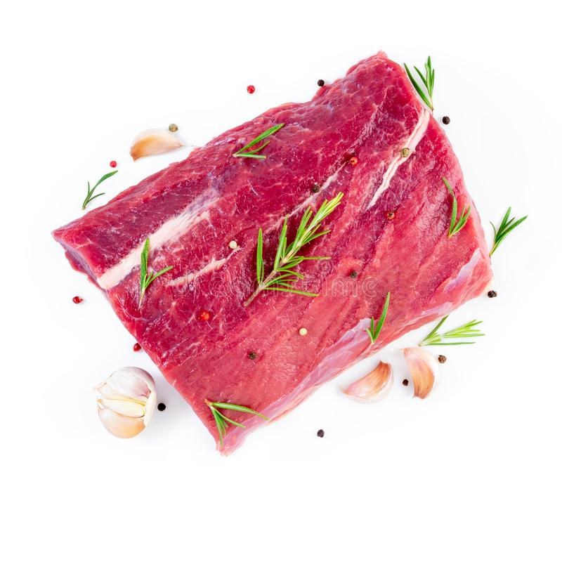 Large piece of meat, raw beef fillet isolated on white background. Striploin with rosemary, garlic seasonings, top view royalty free stock photo