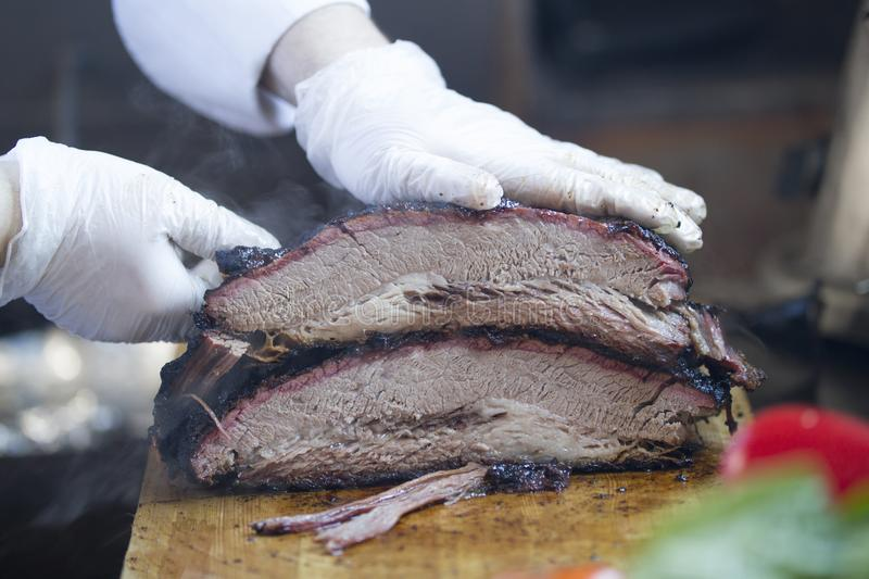 Large piece of smoked meat on a wooden board carved by butcher royalty free stock photo