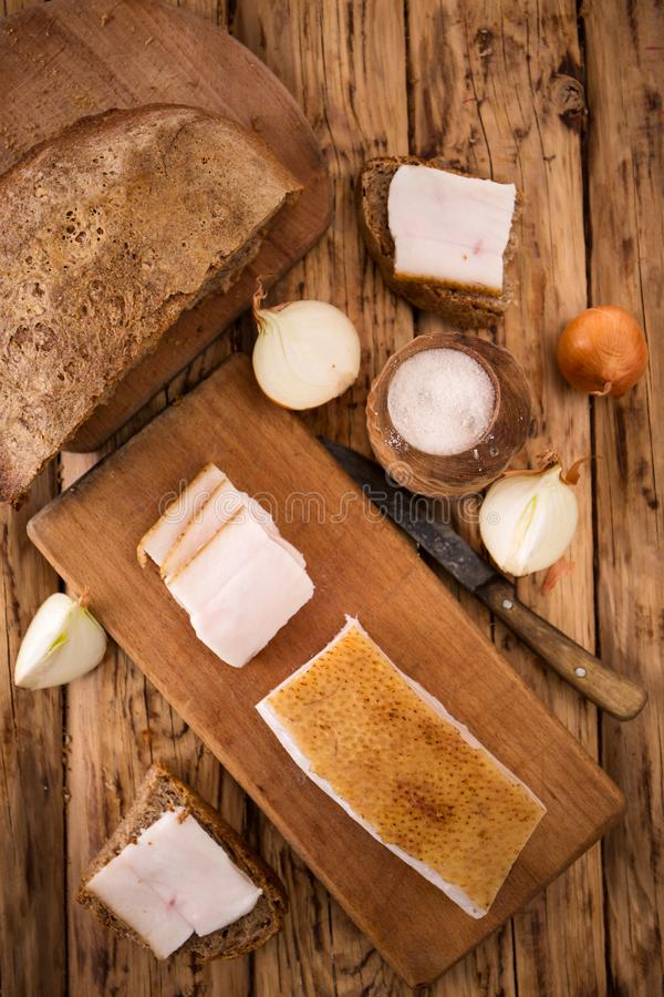 Ukrainian still life with lard. A large piece of Ukrainian lard on a wooden background royalty free stock photography