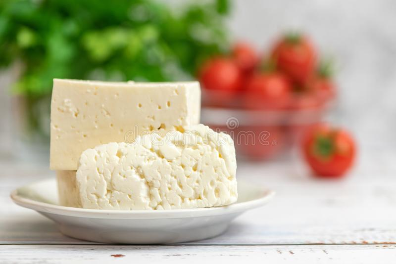 Large pieces of feta cheese in white plate and cherry tomatoes on light background. Selective focus, High key.  royalty free stock photos