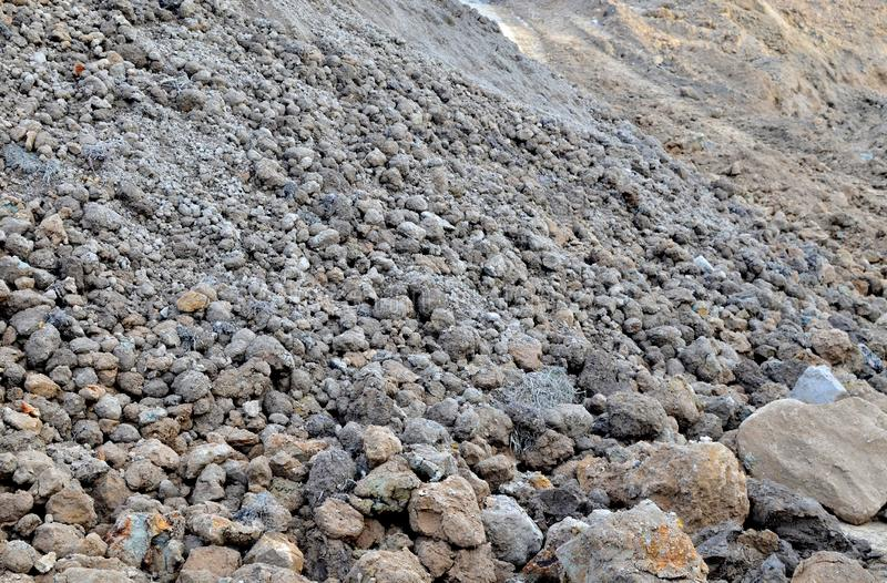 Large pieces of stone clay at the bottom of a mining quarry of minerals, background structure, royalty free stock image