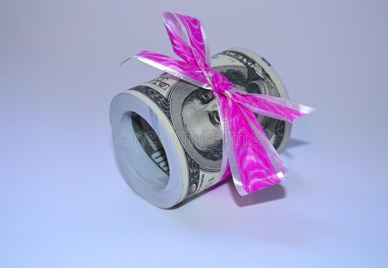 A large pile of dollars tied with a pink ribbon stock photography