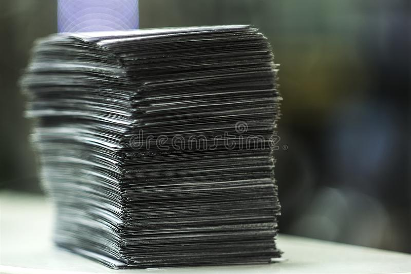 A large Pile of square white sheets, ruler and pencil lies on a brown table. The photo of the stack of paper can be used as a back royalty free stock photos