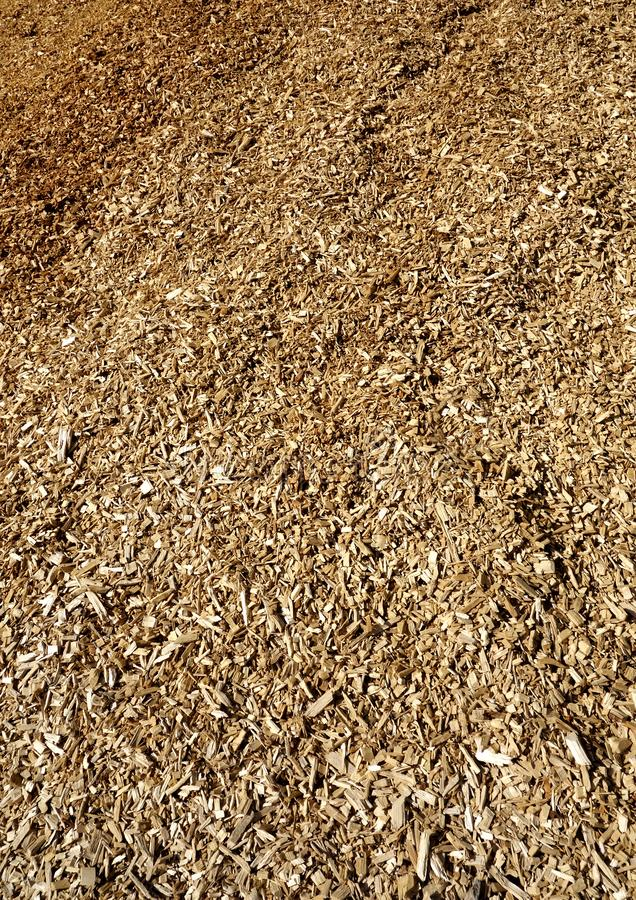 Large Pile of Wood Chips. A closeup detailed textured image of a giant hill of wood chips used as a biomass heating fuel for woods furnaces royalty free stock images