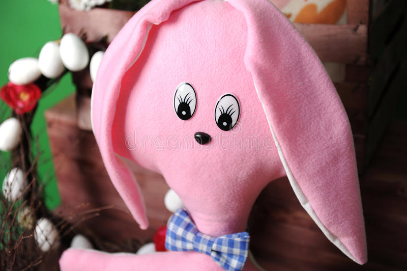 Large pink soft bunny in plaid bow tie with Easter decoration royalty free stock photos