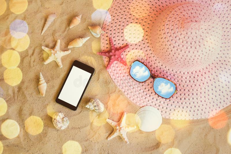 Large pink summer hat, sunglasses, smartphone, starfishes and seashells on sand beach. stock image