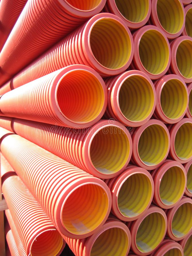 Large plastic tubes. Plastic red corrugated pipes of large diameter for the installation of sewage and water supply stock photos