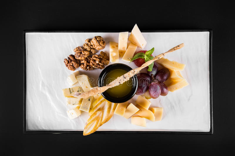 A large plate with a wide selection of snacks like grapes, cheese, walnuts, crackers on dark background. top view stock photo