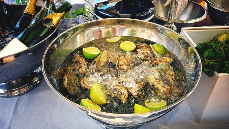 A large platter with delikatesnye oysters on ice with lime served with champagne and herbs. Serving. stock image