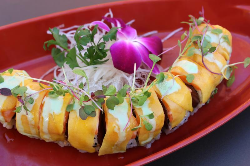 Long sushi roll filled with the freshest ingredients covered in mango slices. Large platter with sliced sushi roll filled with the freshest seafood ingredients stock images