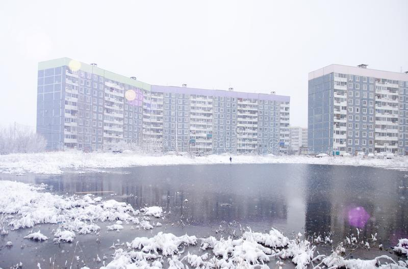 Large pond near a multi-storey building in winter with fresh snow.  royalty free stock image
