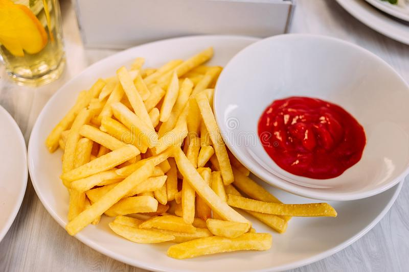 Large portion of French fries and tomato ketchup. On a white plate stock photos