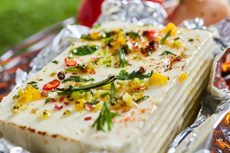 Large portion of halloumi or tofu on a barbecue. Grilling on a sheet of aluminium foil and seasoned with herbs, spices, oil and chili pepper in a close up view stock images