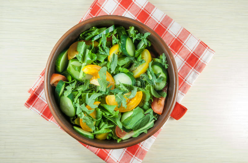 A large portion of salad. With fresh basil leaves, arugula, parsley, tomatoes. On a table with a tablecloth. Top view, copy space stock image