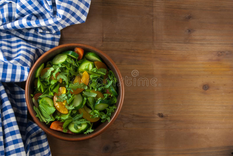A large portion of salad. With fresh basil leaves, arugula, parsley, tomatoes. On a wooden table with a tablecloth. Top view stock photography