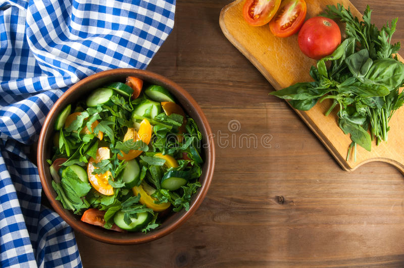 A large portion of salad. With fresh basil leaves, arugula, parsley, tomatoes. On a wooden table with a tablecloth. Top view stock photo