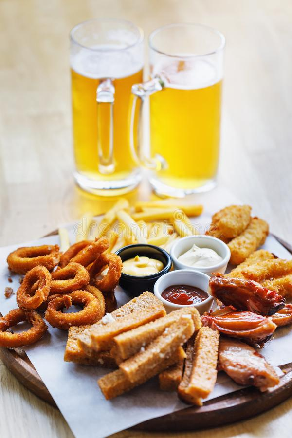 Large portion of snacks and 2 glasses of light beer.  royalty free stock images