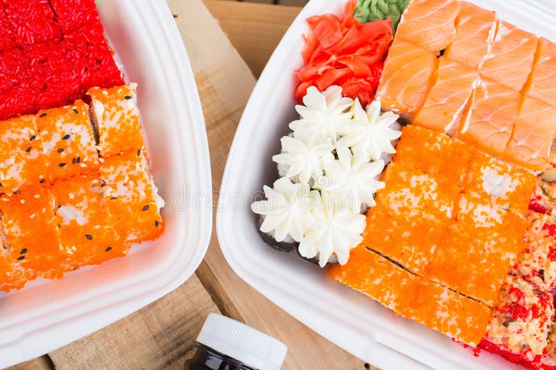 A large portion of sushi rolls. Sushi in a white container, on a wooden background. Flatley view from above royalty free stock image