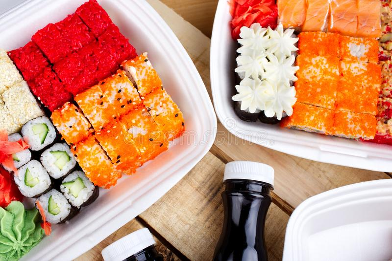 A large portion of sushi rolls. Sushi in a white container, on a wooden background. Next soy sauce royalty free stock photos