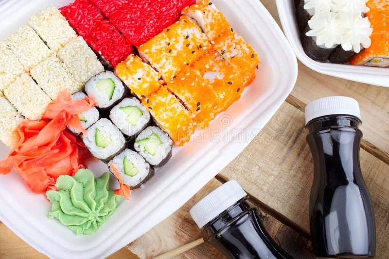 A large portion of sushi rolls. Sushi in a white container, on a wooden background. Next soy sauce royalty free stock images