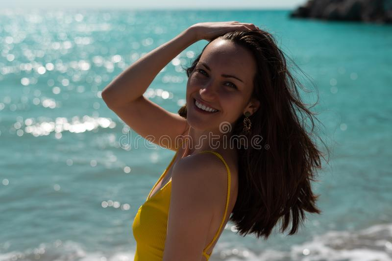 Large portrait in the hard light of the bright sun of a young woman on the sea in a yellow swimsuit, real life royalty free stock photography