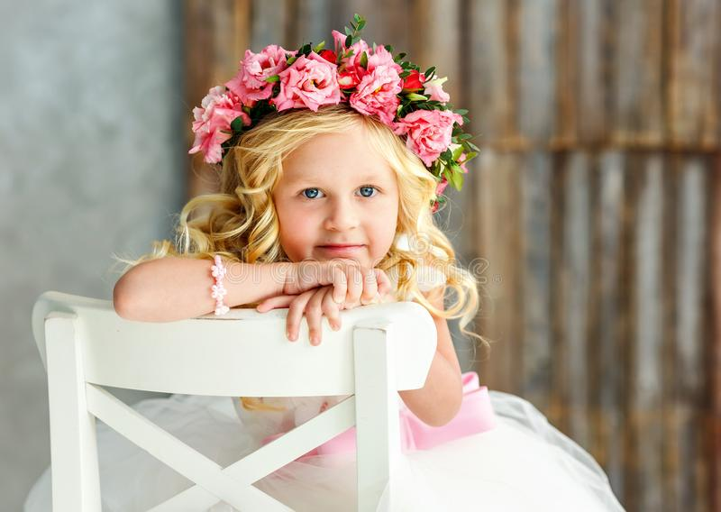 Large portrait of lovely cute little girl - blonde in a wreath of live roses in a white beautiful dress in a bright studio. Close- royalty free stock photography