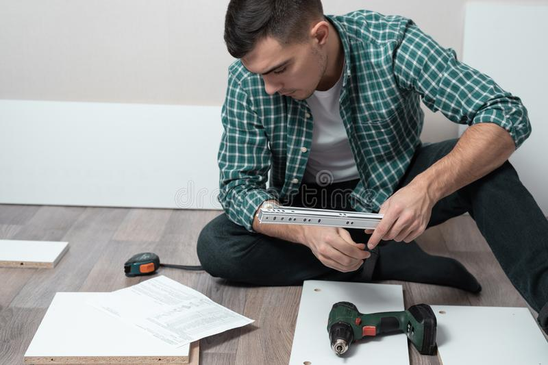 Large portrait of a man sitting on the floor of the room with tools collect furniture according to instructions royalty free stock images
