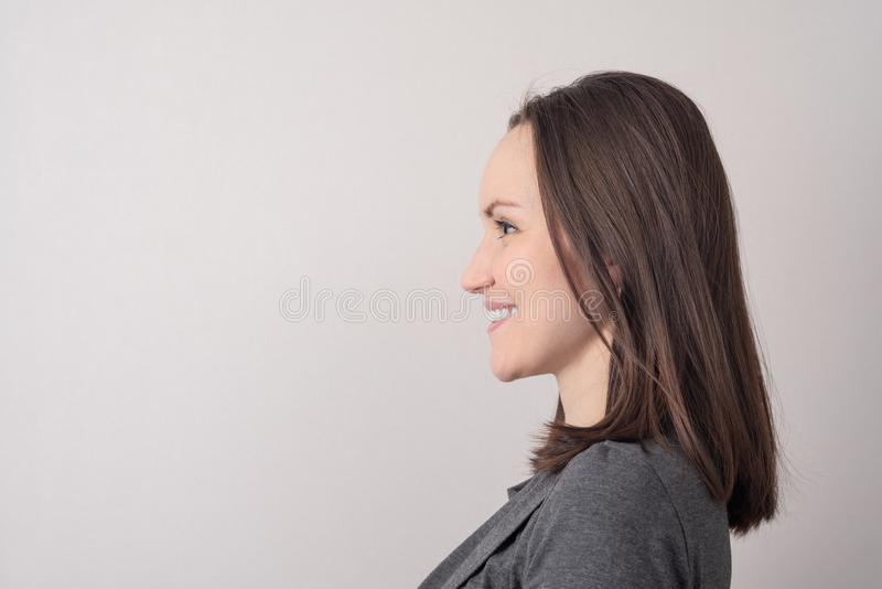 Large portrait of a smiling young brunette in profile on a gray background with a copy of space royalty free stock images