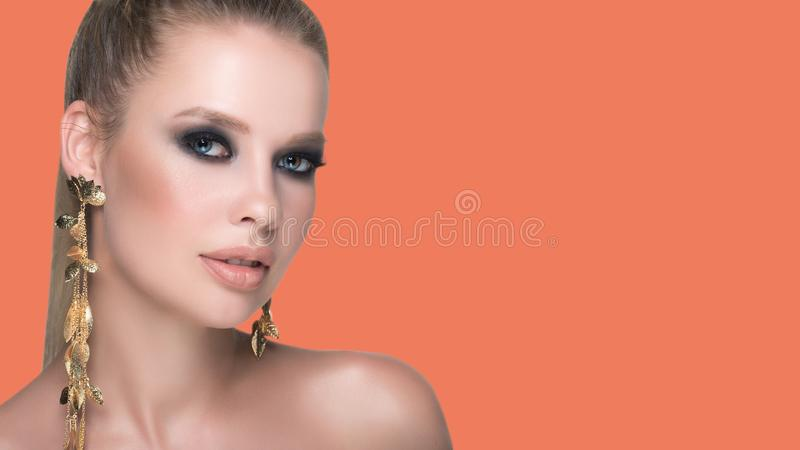 Large portrait of a young beautiful woman with smooth and healthy facial skin on an orange background with copyspace. Gold large royalty free stock image