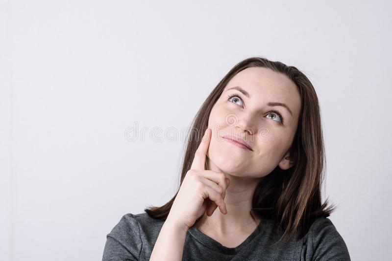 Large portrait of a young European woman on a gray background, hand touches cheek, dreamy look royalty free stock photos