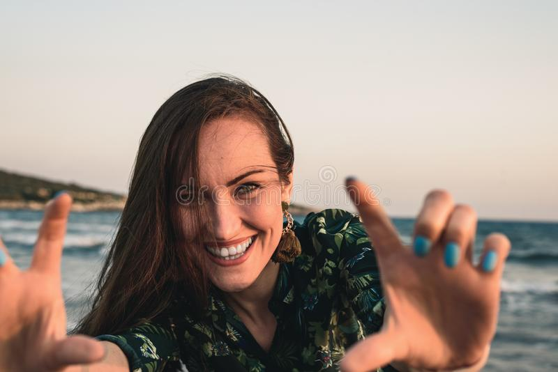 Large portrait of a young woman on the beach at red sunset, selfie, smile, fun, vacation royalty free stock photos