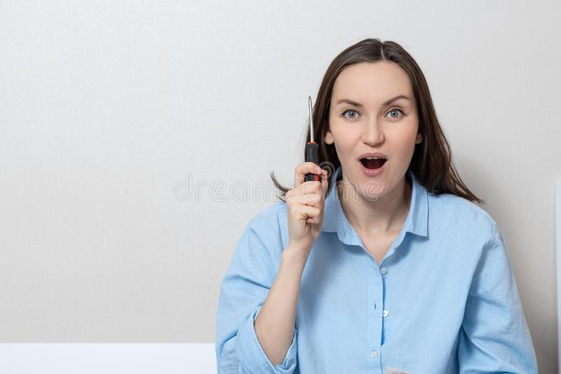 Large portrait of a young woman with a screwdriver in her hands, a copy of the space.  stock photo