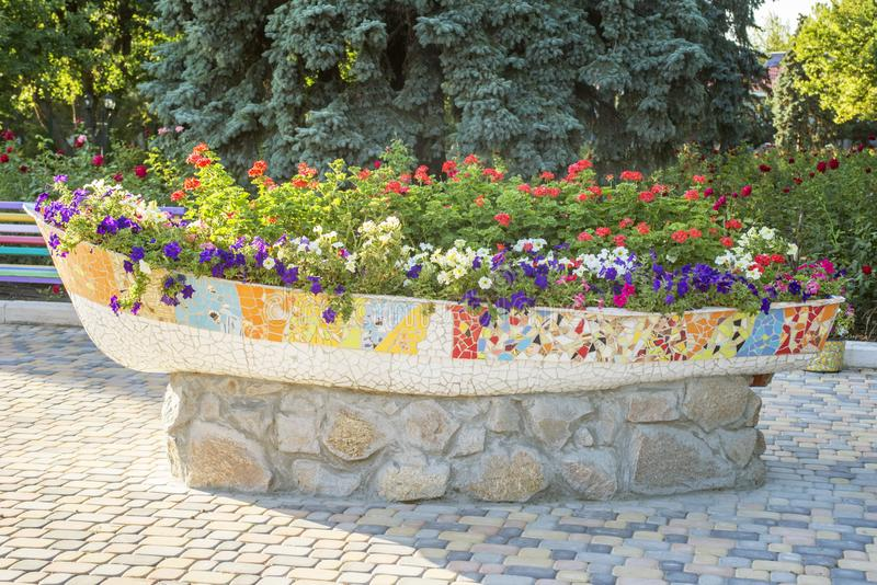 A large pot of flowers on the street. Street flowers in a pot of stone in the shape of a boat stock images