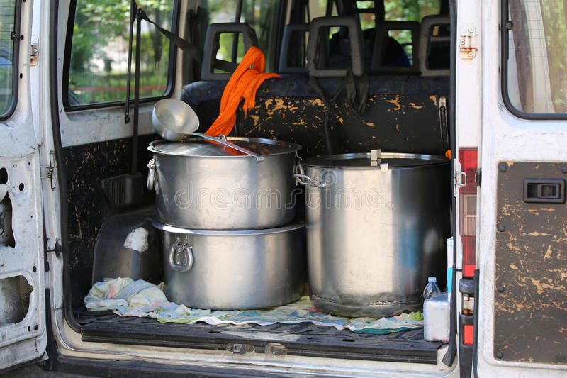 Large pots for transporting food in a van of non-governmental or. Three large pans for transporting food in a van of non-governmental organizations in a refugee royalty free stock photos